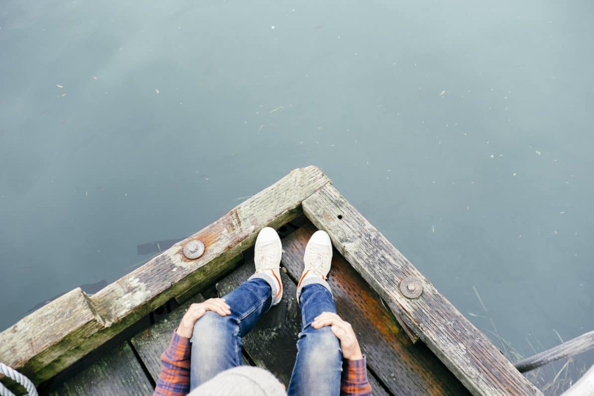 Person sitting on a dock wearing shoes with custom orthotics