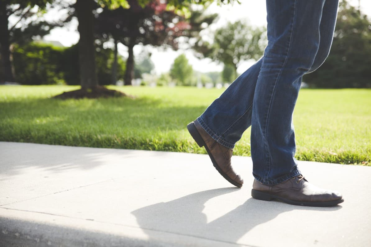 Man with knee osteoarthritis walking on sidewalk with knees and lower legs visible.