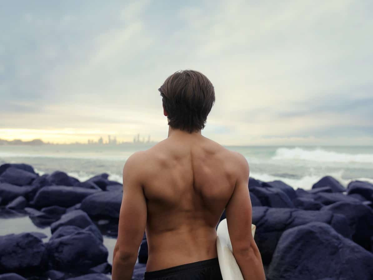 Surfer standing by water with lower back pain.