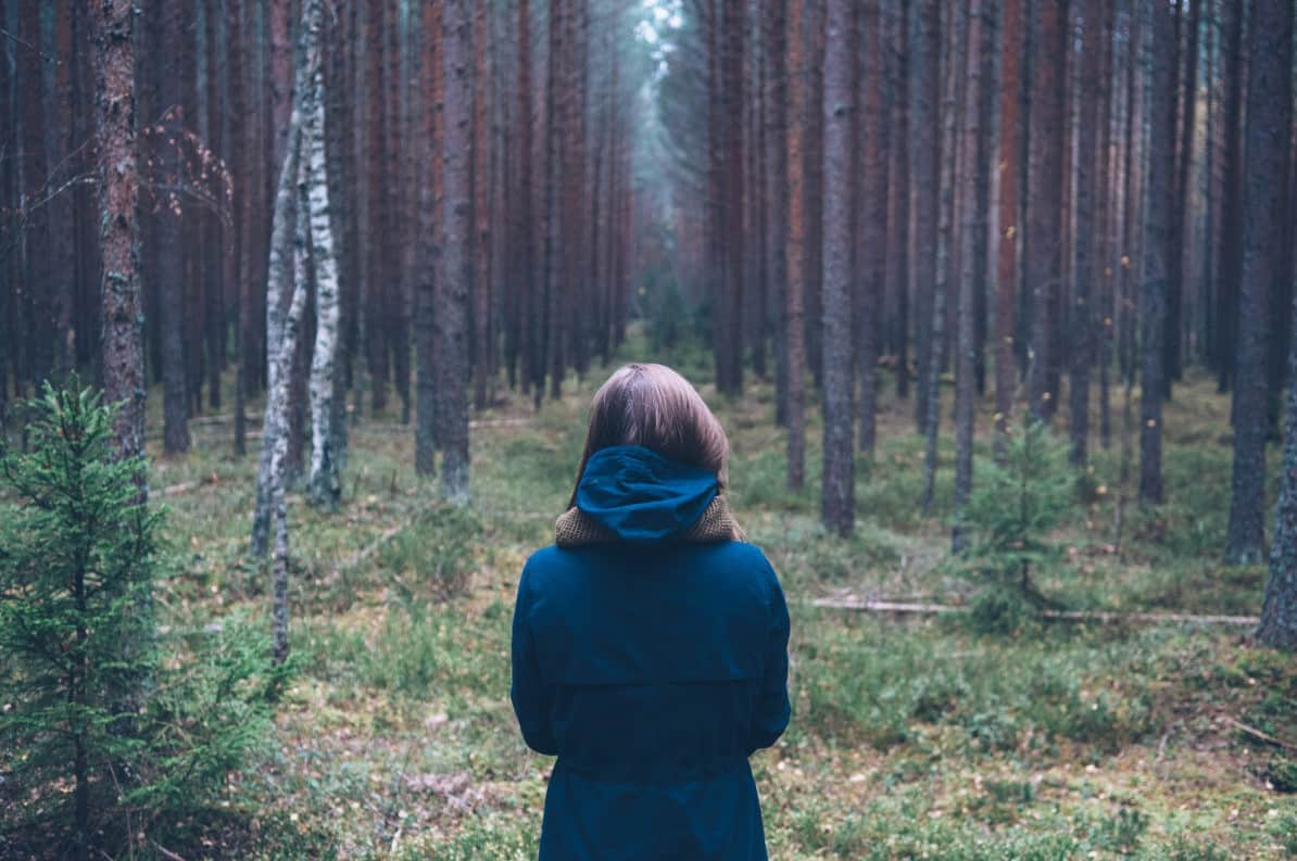 Woman with low back pain facing a forest